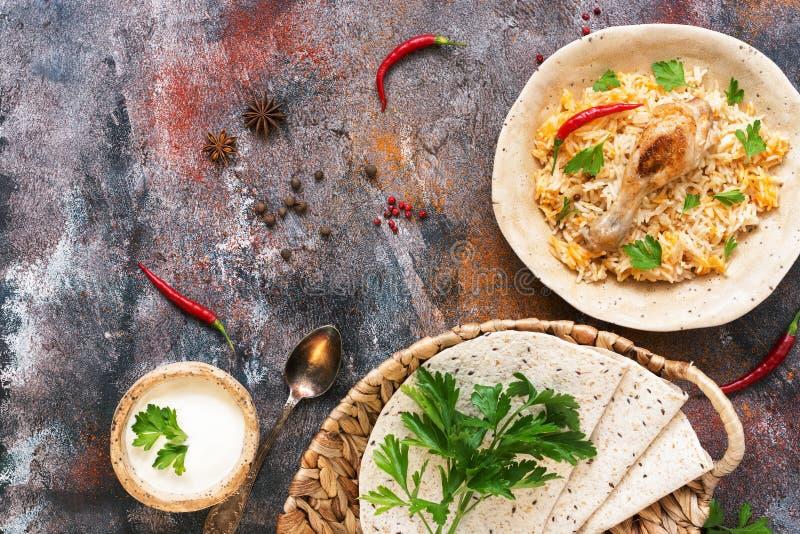Biryani picante delicioso da galinha em um fundo rústico com especiarias, alimento indiano picante tradicional, refeição de Iftar foto de stock