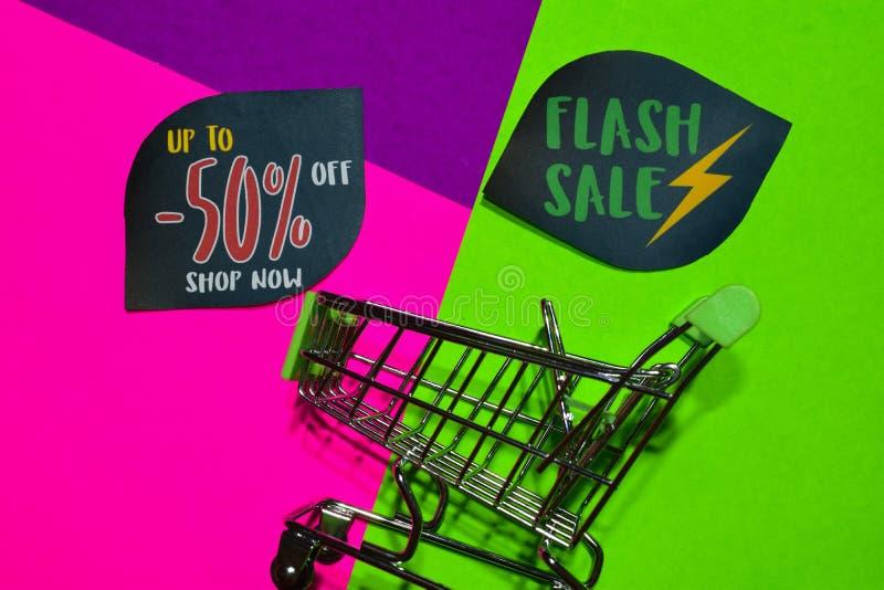 Bis 50% weg vom Geschäft jetzt und greller Verkaufs-Text und Einkaufswagen lizenzfreies stockbild