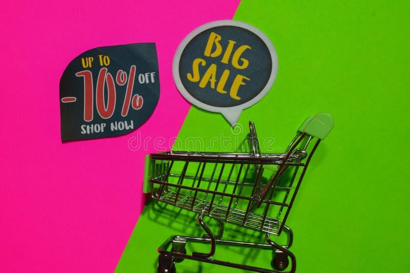 Bis -70% weg vom Geschäft jetzt und großer Verkaufs-Text und Einkaufswagen stockbilder