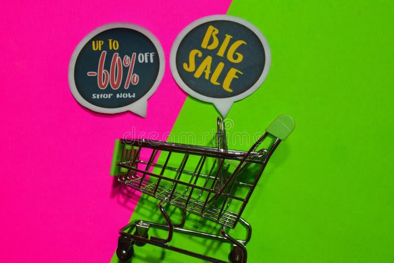 Bis -60% weg vom Geschäft jetzt und großer Verkaufs-Text und Einkaufswagen stockbilder