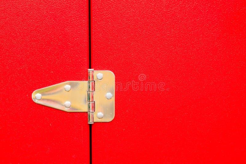Bisagra de acero del metal en puerta roja imagenes de archivo