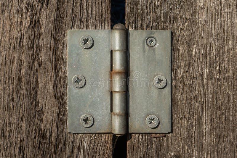Bisagra del metal en tablones de madera marrones con muchos tornillos en ella fotografía de archivo libre de regalías