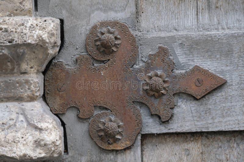 Bisagra forjada vieja decorativa en una puerta de madera fotografía de archivo libre de regalías