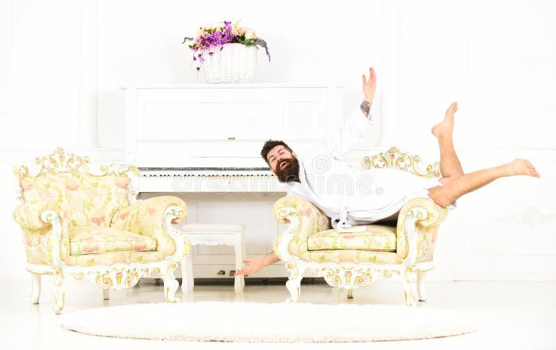 Bisarr man som poserar i fåtölj Udda grabb som ligger på antikt möblemang Miljonär i vitt hotellrum royaltyfria bilder