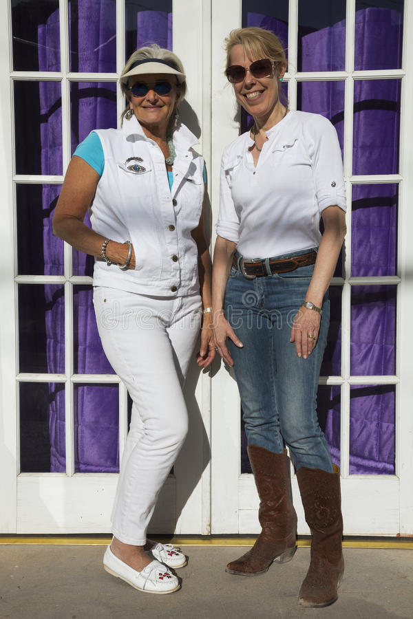 Bisbee, Arizona, USA, April 6, 2015, Phylis Tampio and Leslie Plimpton pose in front of purple draped doorway stock images