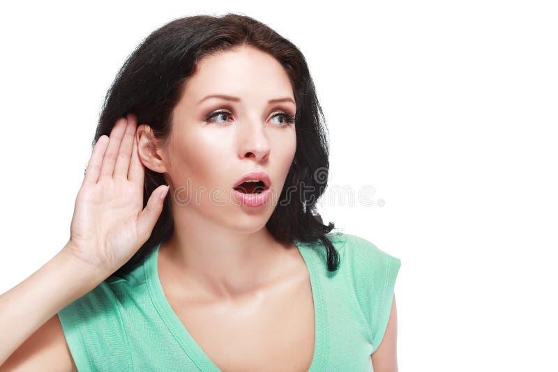Bisbolhetice de escuta da mulher fotografia de stock