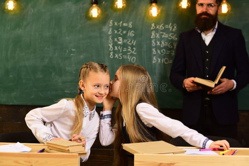 Bisbolhetice que sussurra, meninas que sussurram a bisbolhetice na lição da escola sussurro da bisbolhetice de dois amigos de men fotografia de stock