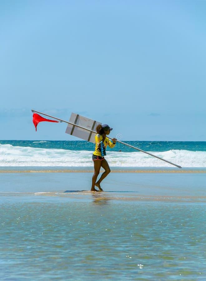 BISCARROSSE FRANKRIKE - JULI 17, 2018: Livräddare på stranden med en röd flagga som varnar simmare att inte skriva in vattnet royaltyfri bild