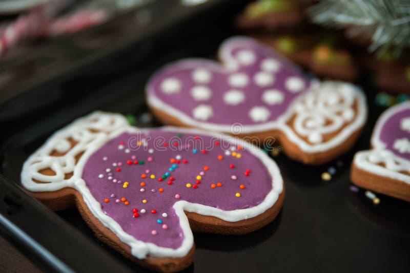 Biscoito do gengibre sob a forma de um mitene em um esmalte violeta, aising em um fundo preto O conceito do cozimento para o Nata imagens de stock royalty free