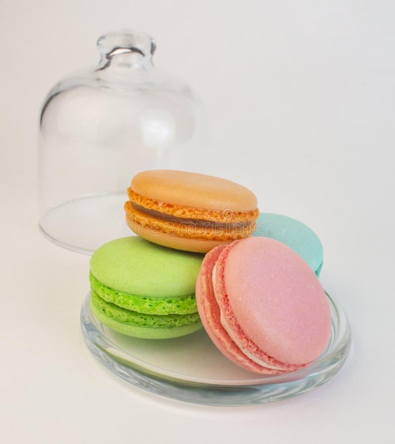 Biscoitos coloridos da pastelaria do bolinho de amêndoa em um caso de vidro no branco Produtos de forno doce dos macarons do fran fotografia de stock royalty free