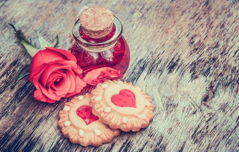 Biscoitos com corações e elixir do amor Dia do `s do Valentim Ajuste para amantes Veneno doce Philtre na garrafa redonda fotografia de stock