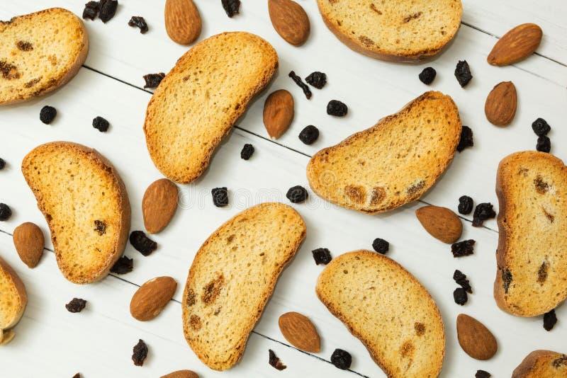 Biscoitos com passas, am?ndoas e as bagas secadas em um fundo de madeira branco, caf? da manh? diet?tico imagens de stock royalty free