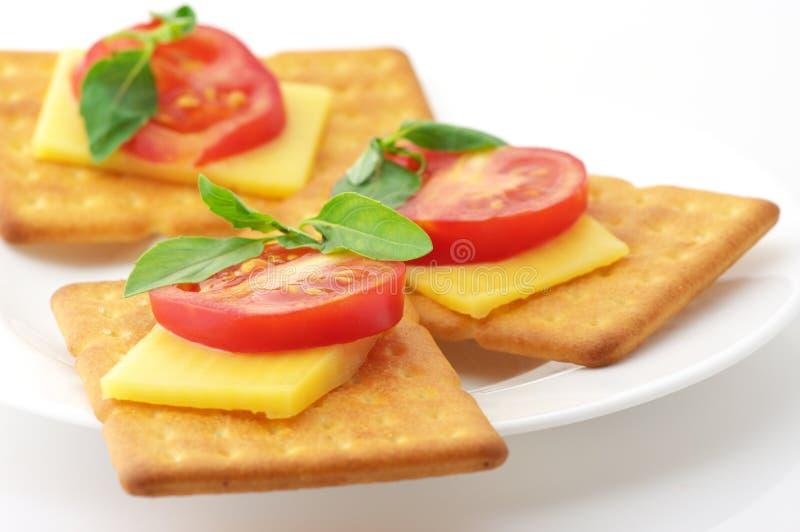 Biscoitos com queijo, tomate e manjericão imagens de stock