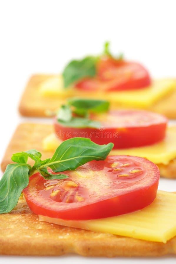 Biscoitos com queijo, tomate e manjericão imagem de stock