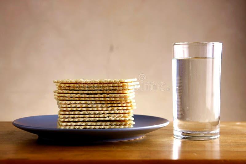 Biscoitos de soda e vidro da água imagem de stock