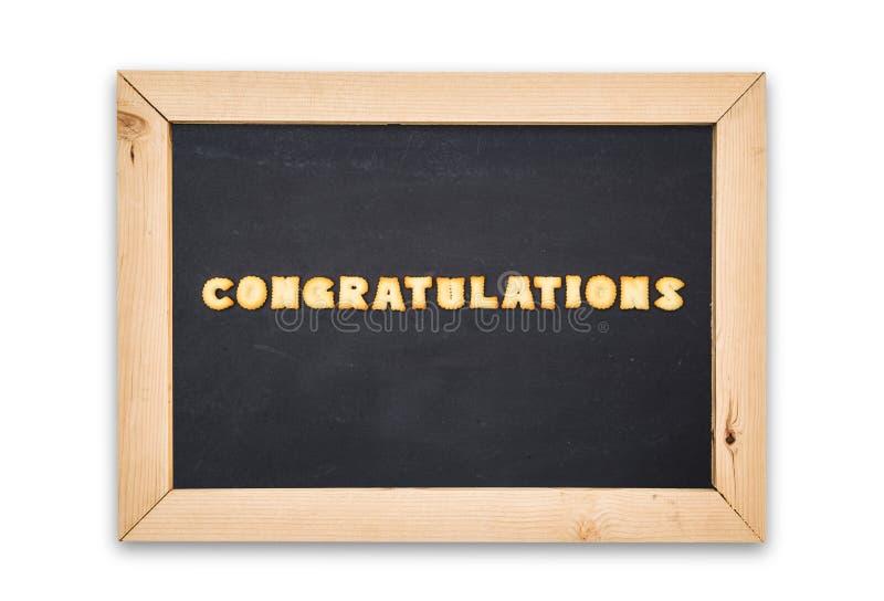 Biscoitos do alfabeto, felicitações da palavra no quadro no fundo branco imagem de stock