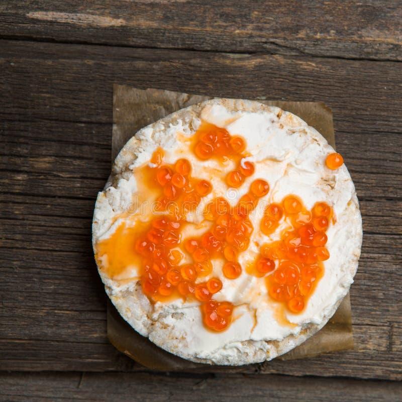 Biscoitos do arroz com propagação do salmão fumado na superfície de madeira velha imagens de stock