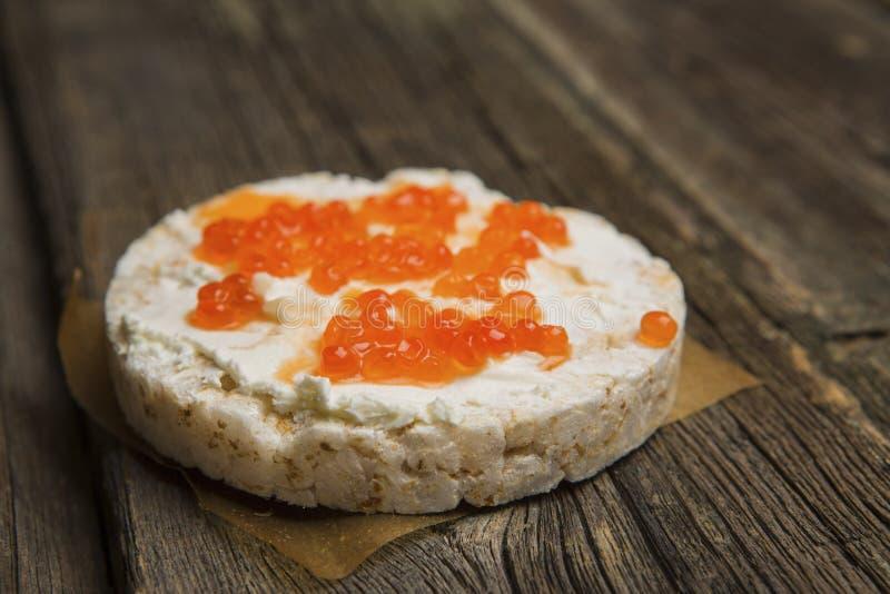 Biscoitos do arroz com propagação do salmão fumado na superfície de madeira velha imagem de stock royalty free