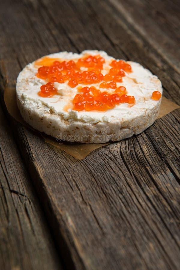 Biscoitos do arroz com propagação do salmão fumado na superfície de madeira velha fotos de stock