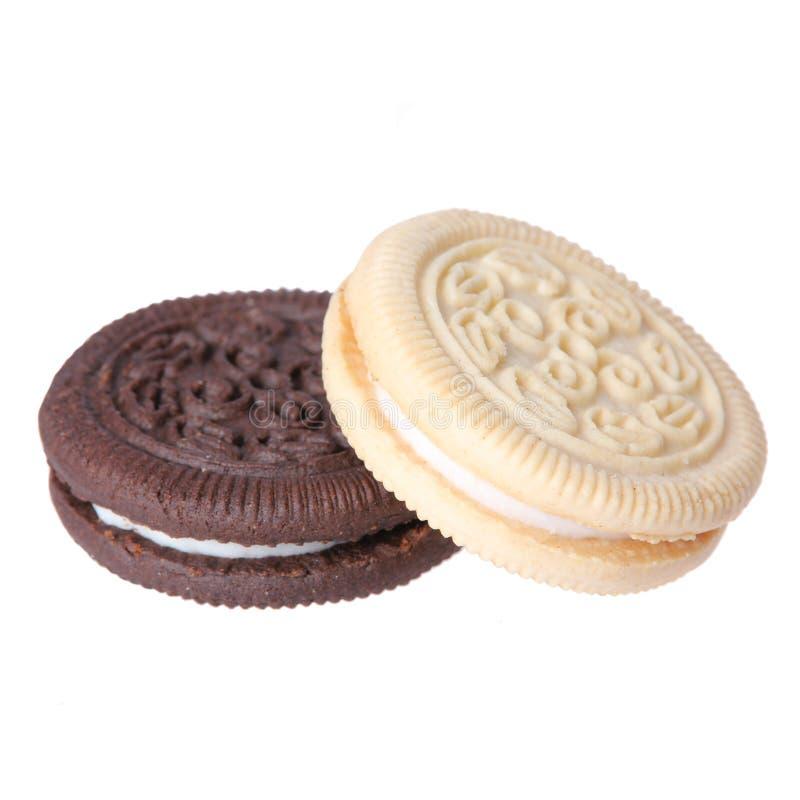 Biscoitos do chocolate e da baunilha com o arquivamento da nata isolado no fundo branco. imagem de stock royalty free