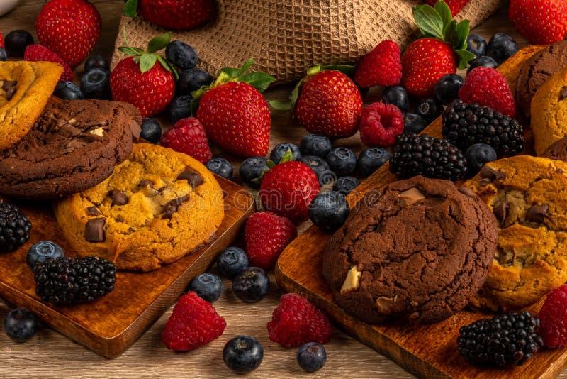 Biscoitos do chocolate na bandeja de madeira com close-up dos frutos da floresta imagem de stock