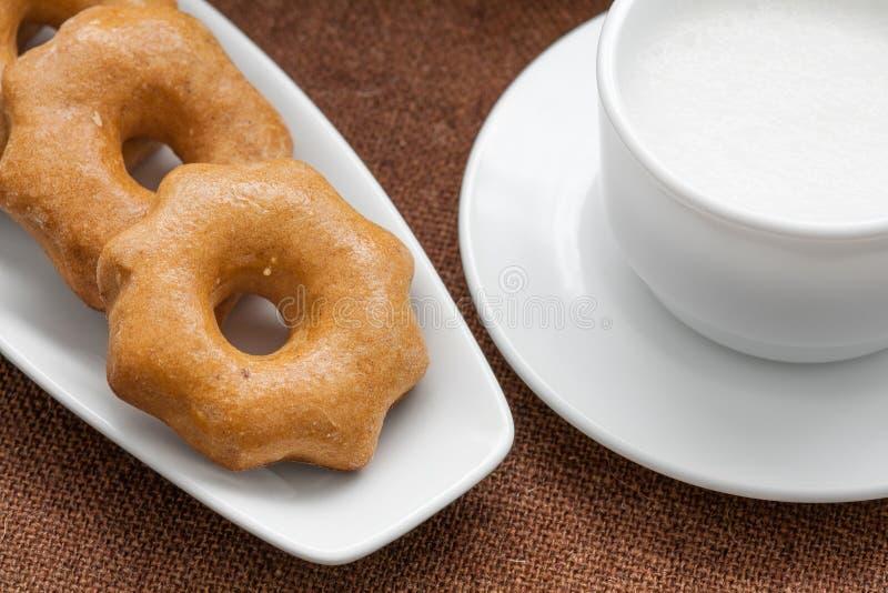 Biscoitos do mel em uma placa e em um copo do leite fotos de stock royalty free