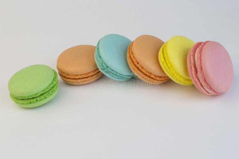 Biscoitos doces do bolinho de am?ndoa, pastelarias francesas de cores diferentes em um fundo branco, macarr?o dispersado em uma t imagens de stock royalty free