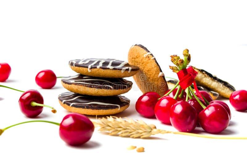 Biscoitos e frutos da cereja isolados fotografia de stock royalty free