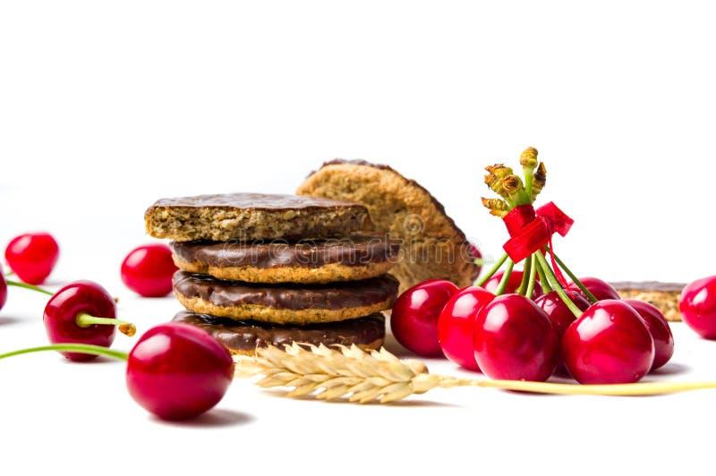 Biscoitos e frutos da cereja isolados imagem de stock
