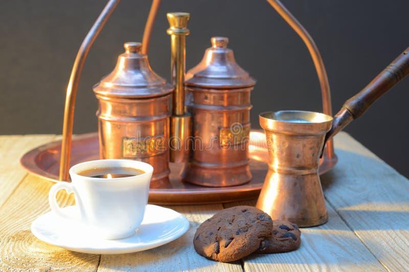 Biscoitos e uma xícara de café perto do açucareiro e do recipiente com café na tabela de madeira rústica fotografia de stock royalty free