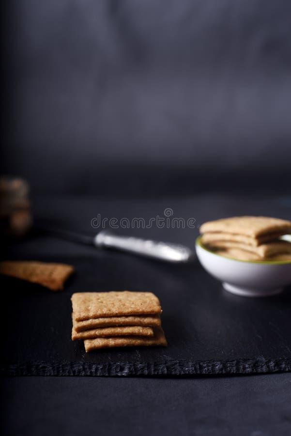 Biscoitos inteiros caseiros do trigo no fundo escuro fotos de stock royalty free