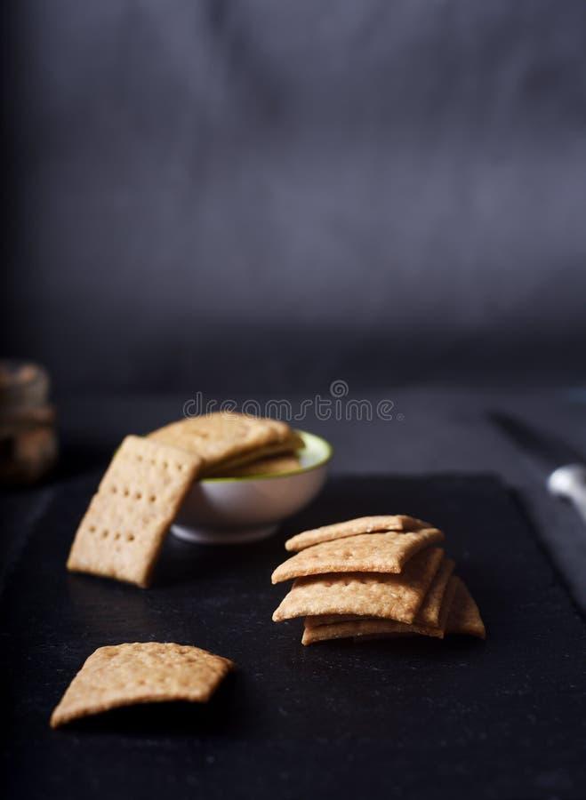 Biscoitos inteiros caseiros do trigo no fundo escuro imagens de stock