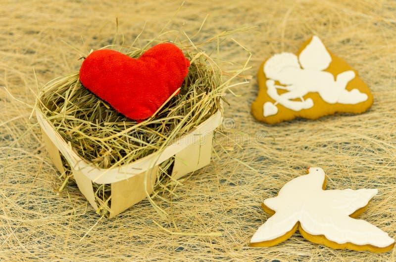 Biscoitos vermelhos do coração e do gengibre sob a forma de um cupido e de uma pomba branca Cesta de vime e cookies fotografia de stock