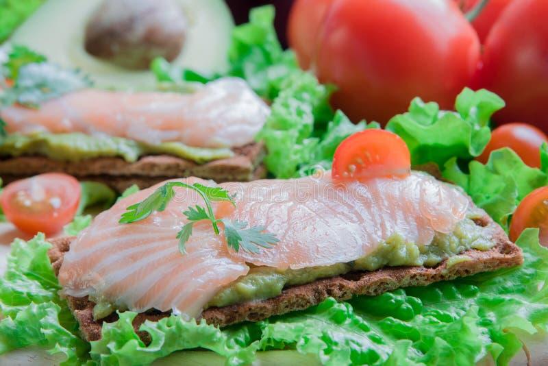 Biscote curruscante con guacamole y salmones foto de archivo