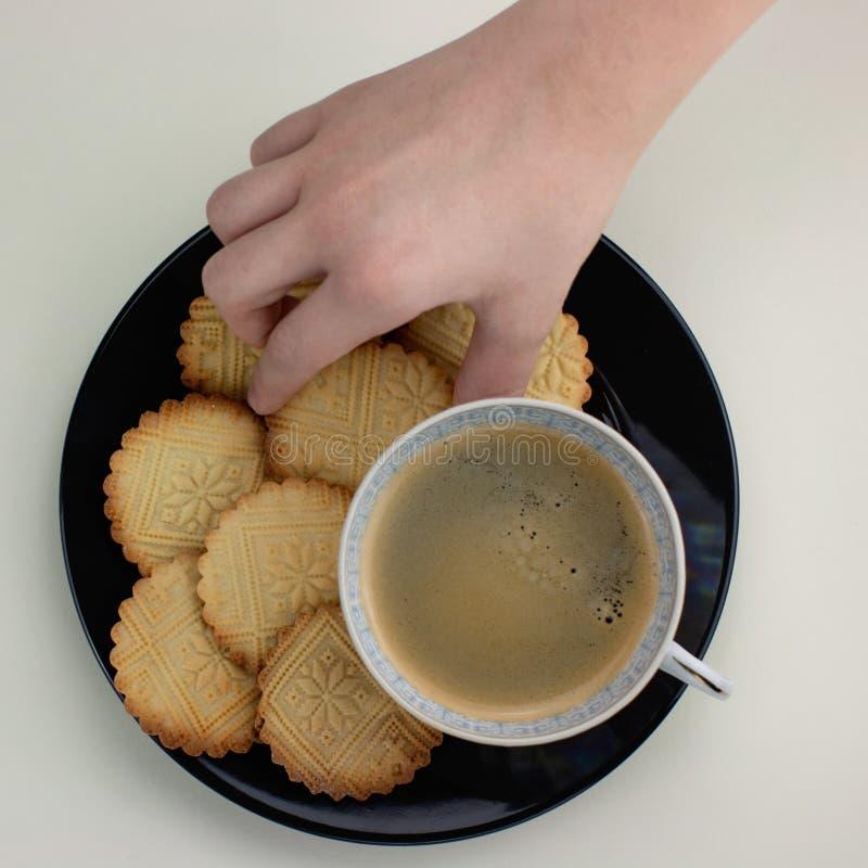 Biscotti al burro modellati casalinghi sulla banda nera e sulla tazza con caffè nero I bambini passano a tenuta un biscotto Vista immagini stock libere da diritti