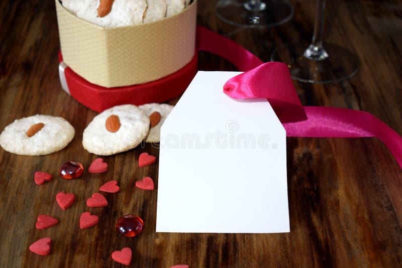 Biscotti bianchi con la mandorla in una scatola in forma di cuore I cuori minuscoli sono sparsi intorno fotografia stock