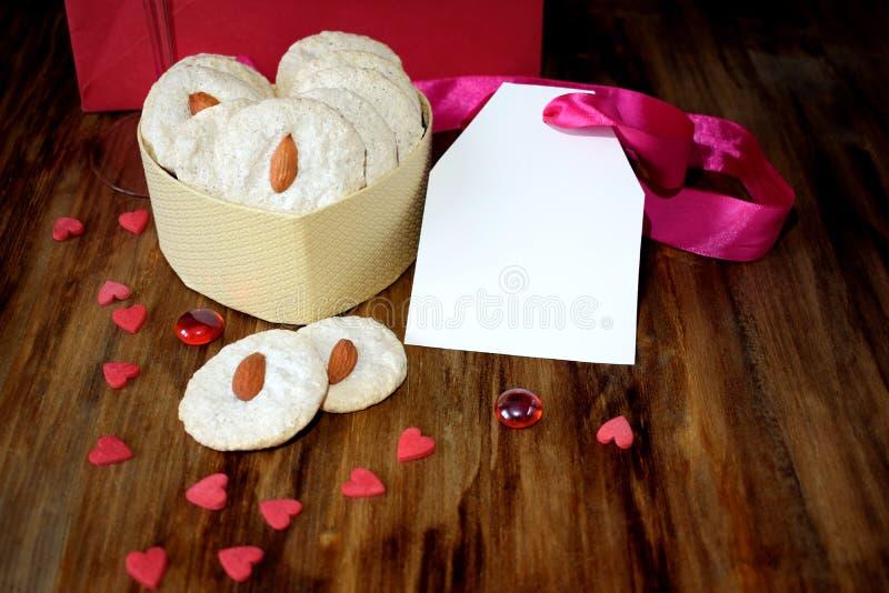 Biscotti bianchi con la mandorla in una scatola in forma di cuore I cuori minuscoli sono sparsi intorno immagine stock