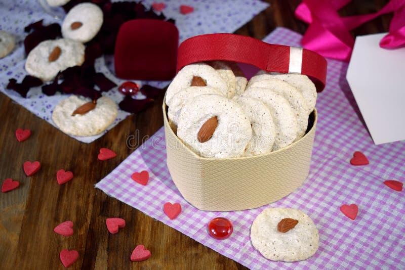 Biscotti bianchi con la mandorla in una scatola in forma di cuore I cuori minuscoli sono sparsi intorno fotografia stock libera da diritti