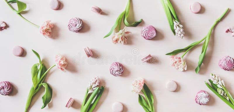 Biscotti, caramelle gommosa e molle e fiori di Macaron sopra fondo rosa, vista superiore fotografia stock