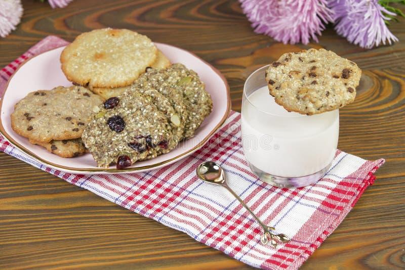 Biscotti casalinghi: noce di cocco, farina d'avena, cioccolato, su una tavola di legno, con un bicchiere di latte, contro lo sfon fotografia stock libera da diritti