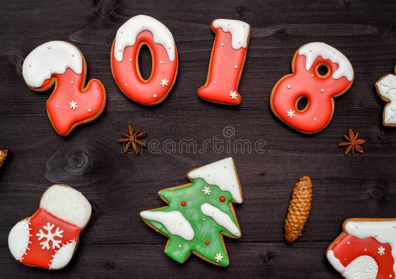 Biscotti casalinghi saporiti del pan di zenzero di Natale sulla tavola di legno, vista superiore Numeri al forno della caramella  fotografia stock libera da diritti