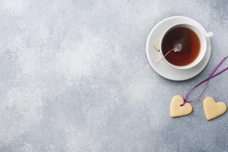 Biscotti casalinghi sotto forma di un cuore e di una tazza di tè su un fondo grigio Copi lo spazio giorno del ` s del biglietto d fotografia stock