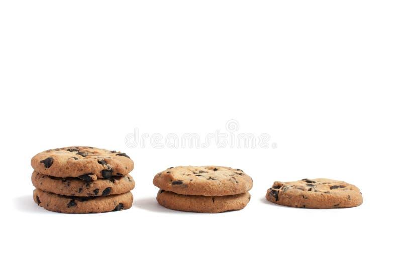 biscotti con cioccolato accatastato in tre pile di tre, di due e di uno su un fondo bianco immagine stock