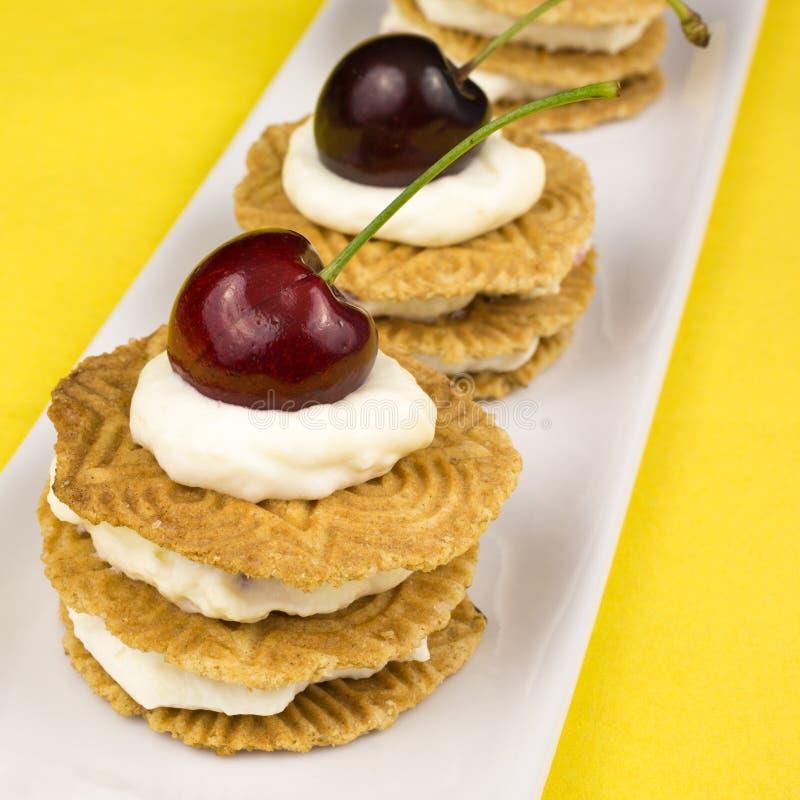 Biscotti con crema e la ciliegia montate fotografia stock