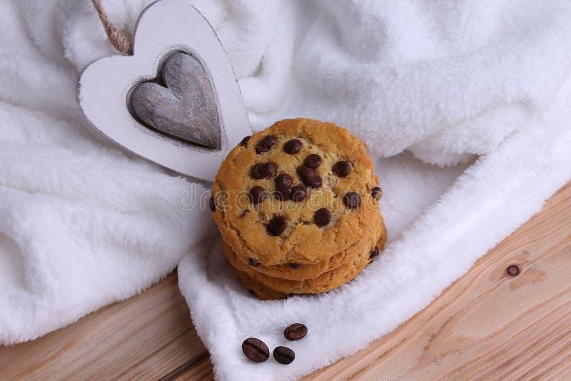 Biscotti con cuore di legno sulla coperta bianca immagini stock libere da diritti