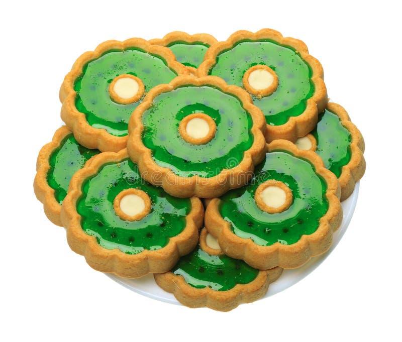 Biscotti con gelatina verde sulla zolla bianca, isolata fotografia stock