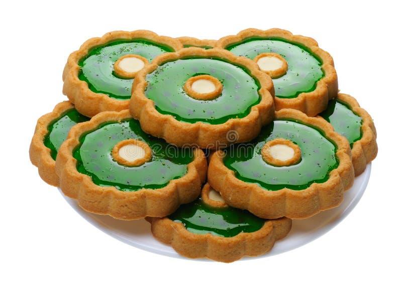 Biscotti con gelatina verde sulla zolla bianca, isolata fotografie stock