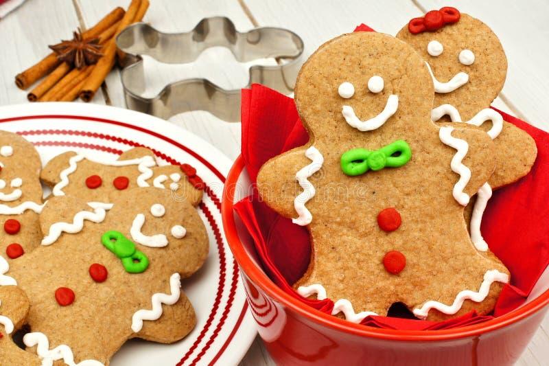 Biscotti degli uomini di pan di zenzero di Natale in ciotola rossa su legno bianco fotografia stock