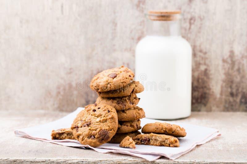 Biscotti del chip della farina d'avena del cioccolato con latte sui tum di legno rustici immagini stock