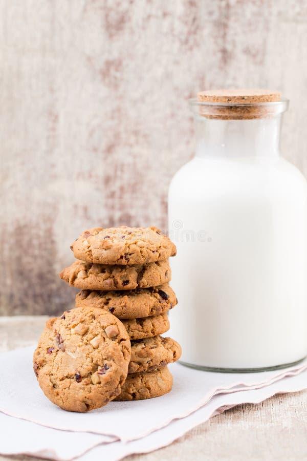 Biscotti del chip della farina d'avena del cioccolato con latte sui tum di legno rustici fotografie stock libere da diritti